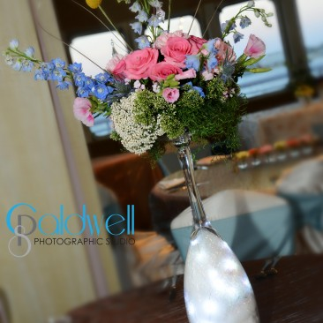 Unique Tall Centerpiece with lit bottom and assortment of  roses, godetia, billy balls, stock, rice flower & wax flower